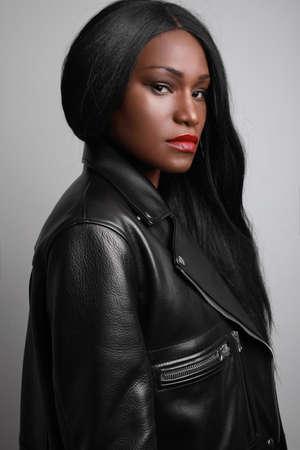 Vertical headshot of young black female model, wearing biker jacket posing over grey wall. Studio Shot.
