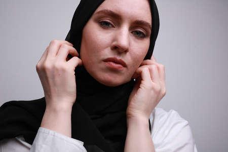 Young Arabian woman wearing hijab posing over white wall.