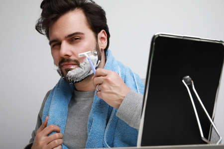 Handsome bearded man in casual clothes iwith beard apply shaving foam posing on gray background, 版權商用圖片