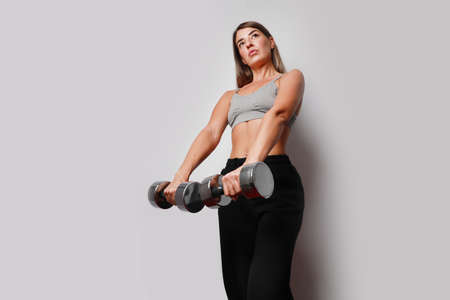 Portrait of sporty young woman doing exercise at home, smiling and posing over white wall.