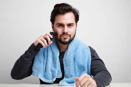 Handsome young man shaving his beard in bathroom, holding shaver machine. Space for text.