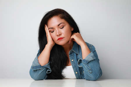 Mature woman with closed eyes, looking sad. Isolated on white background wall. 写真素材