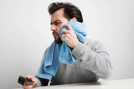 Headshot of bearded young man is shaving. Isolated on white background. 版權商用圖片