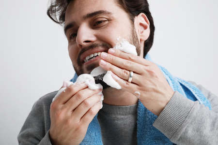 Happy bearded young man, shaving in the morning. Isolated on white background. 版權商用圖片