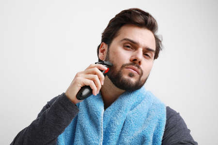 Bearded young man, shaving in the morning. Isolated on white background.