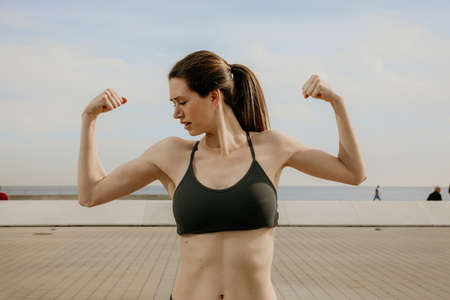 Portrait of young sporty woman showing biceps posing outdoor.