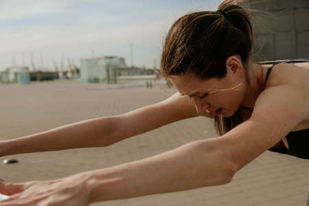 Young woman stretching body after jogging, female stretches body outdoor. Stock fotó