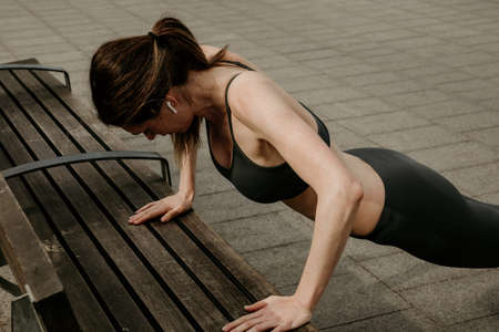 Sporty woman doing pull-ups on the bench outdoor. Lifestyle concept.