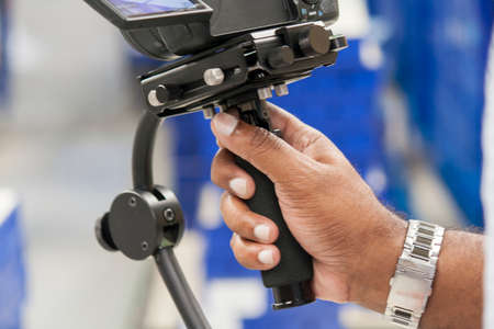 s video: afroamerican hand holding a stabilizer and recorgding to footage
