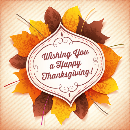 Thanksgiving greeting card with a white label in front of a circle of colorful autumn leaves.