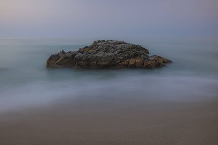 Slow shutter speed photographing water surrounding a rock formation at Coata del Sol, Fuengirola, Spain.