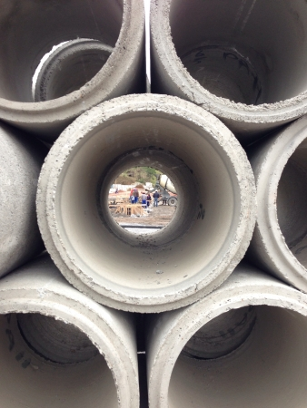 constrution: Seeing workers on a constrution site trought a cement pipe
