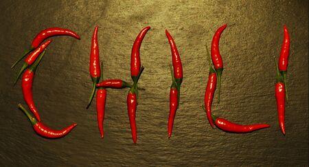 """Photographie de piments rouges sur la forme de mot """"chili"""" sur fond d'ardoise"""