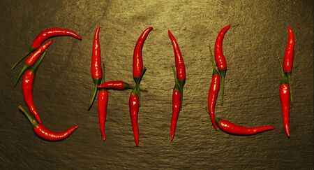 """Photography of red hot peppers set on """"chili"""" word shape on slate background"""