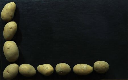 Photography of dusty potatoes on slate background for restaurant menu