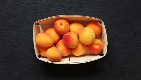 Photography of apricots in a crate on slate background for food illustrations 免版税图像