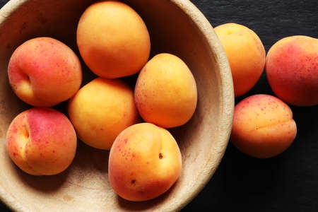 Photography of apricots in a wooden bowl, on slate background for food illustrations 免版税图像