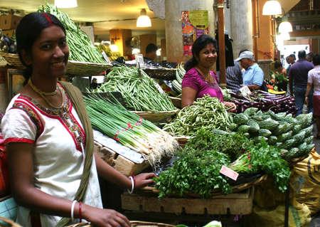 mauritius: twee lachende Aziatische vrouwen de verkoop van groenten in een markt Redactioneel