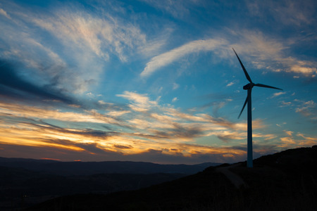 turbine: Una turbina de viento soiltary silouhetted contra un cielo azul y naranja sunsetting Foto de archivo