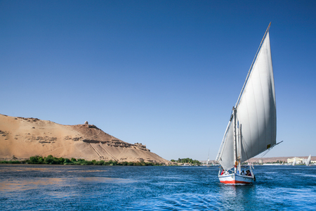 A tradional Nile Felucca sails past ancient egyptian ruins on top of a sandy hill