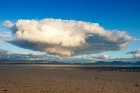 ynys: A huge ominous looking cloud hovering over the beach at Newborough, Anglesey.