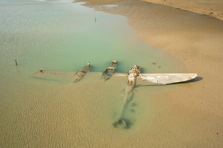 avion de chasse: The wrech of a crashed WW2 P38 Lightning Aircraft laying on a beach in Wales, UK Banque d'images