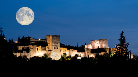 Early evening with full oon over the Alhambra Palace and fortress located in, Granada, Andalusia, Spain. Dark blue sky and the Palace illuminated