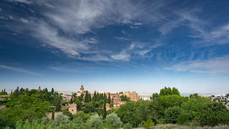 Alhambra Palace and fortress located in, Granada, Andalusia, Spain with deep blue sky and light white clouds.
