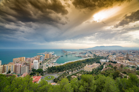 malaga port and malaga city with cathedral against a dramatic sky with clear blue sea