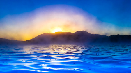 Color enhanced scene of a blue inky sea with a dark mountainous skyline silhouetted against an orange setting sun. A thick mist rises from the water forming clouds which soften the light.