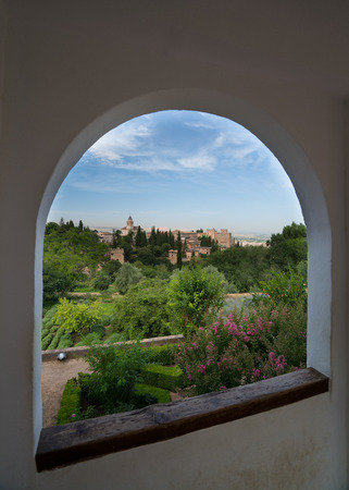 View throuh an arched window of Granada and the Alhambra Palace and fortress located in, Granada, Andalusia, Spain.