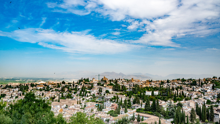 Elevated view of Granada, Andalusia, Spain with mountains in the background against a deep blue sky
