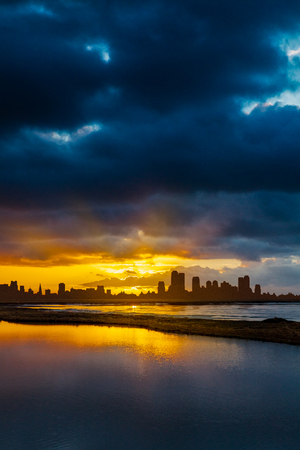 Dramatic blue and orange sky with modern city skyline silhouetted against the sky. An expanse of water in the foreground reflects the drama of the sky. Portrait format with space for copy or text.