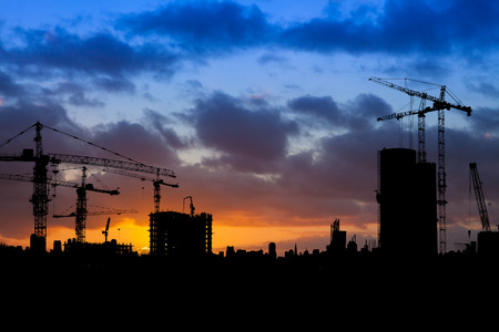 Construction site with cranes silhouetted against a blue and orange sky at sunrise Zdjęcie Seryjne