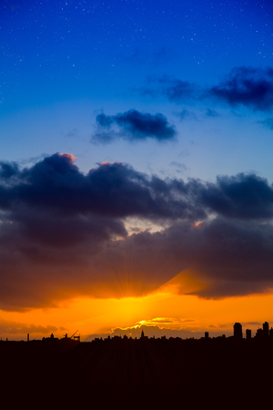 Dramatic blue and orange sky with modern city skyline silhouetted against the sky. Portrait format with space for copy or text