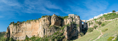 High Resolution Ronda Panorama  showing the entire gorge and cliff on which the Parador is situated also  Puente Nuevo bridge and El Tajo Gorge against a bright blue sky in the City of Ronda in Spain's Malaga province, Andalusia
