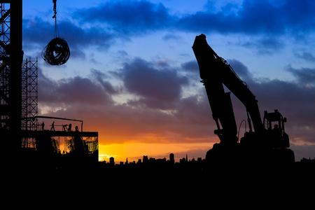 Baustelle mit großen Bagger LKW silhouetted gegen einen blauen und orange Himmel bei Sonnenaufgang Standard-Bild - 81381828