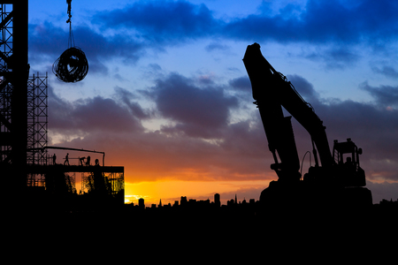 Construction site with  large digger truck silhouetted against a blue and orange sky at sunrise Zdjęcie Seryjne