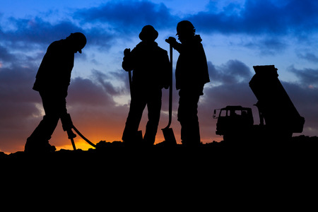 Three construction workers and their truck silhouetted against an orange and blue sunrise sky