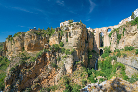Ronda Panorama showing the Parador,  Puente Nuevo and El Tajo Gorge against a bright blue sky in the City of Ronda in Spain's Malaga province, Andalusia Stock Photo