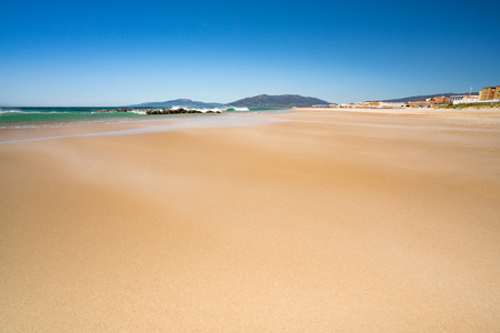 WIld windswept Tarifa Beach, Spain. Sand swirling and surf crashing against a perfect blue sky Stock Photo