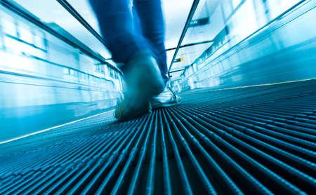 Foot man stepping on moving escalator