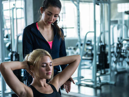 Young woman exercise follow instruction of trainer at the gym Stock Photo