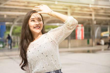 日光から手で顔を覆う若い女の子 写真素材