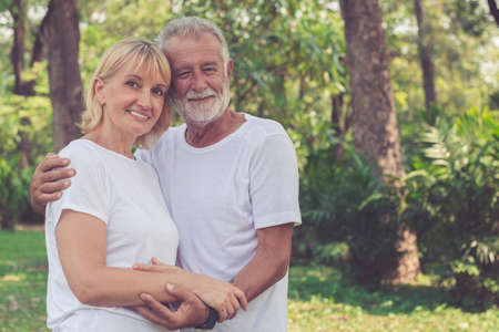 Happy old couple smiling in the park after retirement