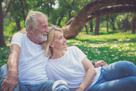Cheerful couple relax while sitting at park