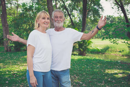 Happy old elderly caucasian couple smiling in park on sunny day Archivio Fotografico