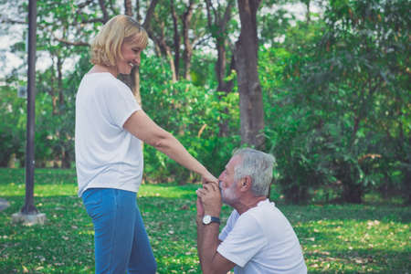 Happy old couple kiss his wife hand at the garden Stok Fotoğraf