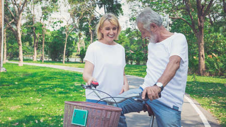 Happy elder couple riding a bicycle in the park