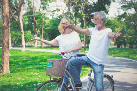 Happy senior couple riding a bicycle in the park Stok Fotoğraf